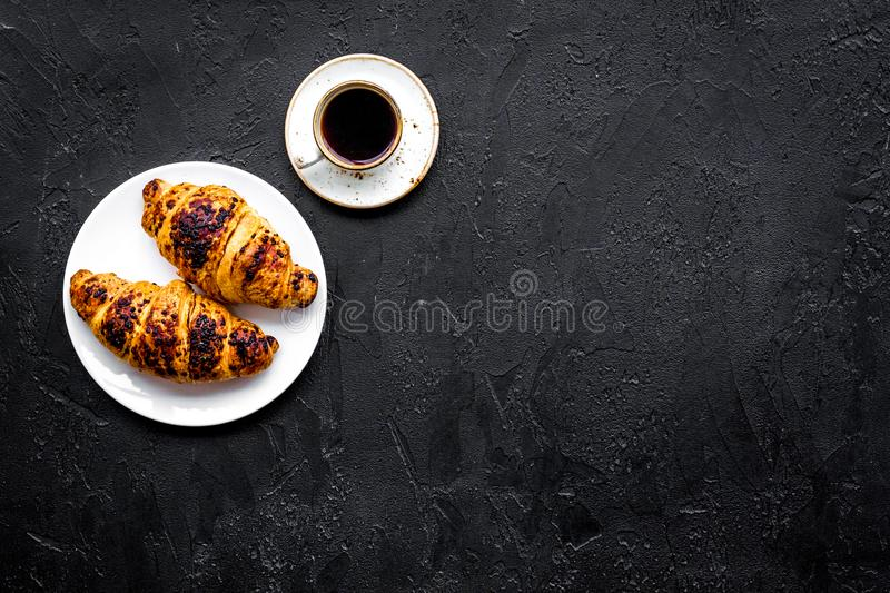 Light breakfast. Small cup of black coffee and croissant on black background top view copyspace. Light breakfast. Small cup of black coffee and croissant on royalty free stock image