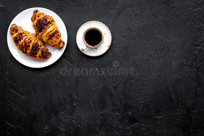 Light breakfast. Small cup of black coffee and croissant on black background top view copyspace. Light breakfast. Small cup of black coffee and croissant on royalty free stock photos