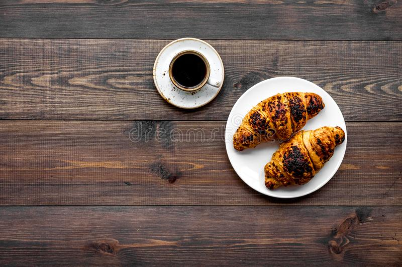 Light breakfast. Small cup of black coffee and croissant on dark wooden background top view copy space. Light breakfast. Small cup of black coffee and croissant stock images