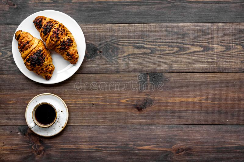 Light breakfast. Small cup of black coffee and croissant on dark wooden background top view copy space. Light breakfast. Small cup of black coffee and croissant stock image