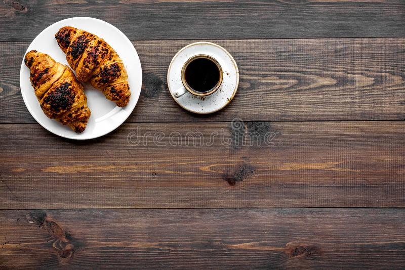 Light breakfast. Small cup of black coffee and croissant on dark wooden background top view copy space. Light breakfast. Small cup of black coffee and croissant stock photos