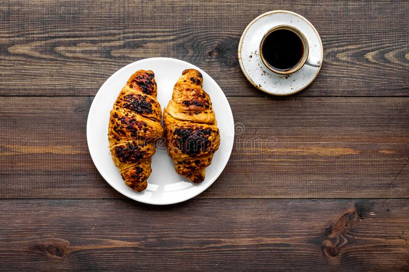 Light breakfast. Small cup of black coffee and croissant on dark wooden background top view copy space. Light breakfast. Small cup of black coffee and croissant stock photography