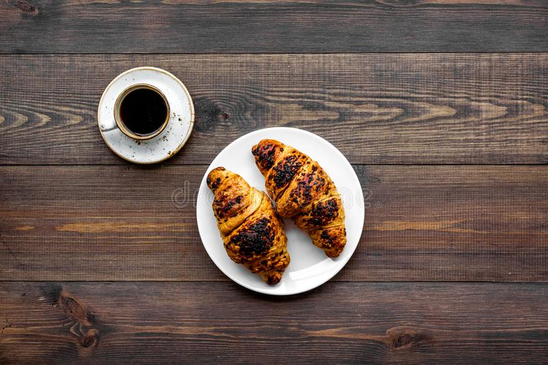 Light breakfast. Small cup of black coffee and croissant on dark wooden background top view copy space. Light breakfast. Small cup of black coffee and croissant stock photo