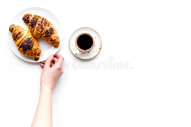 Light breakfast. Small cup of black coffee and croissant on white background top view copyspace. Light breakfast. Small cup of black coffee and croissant on stock photo