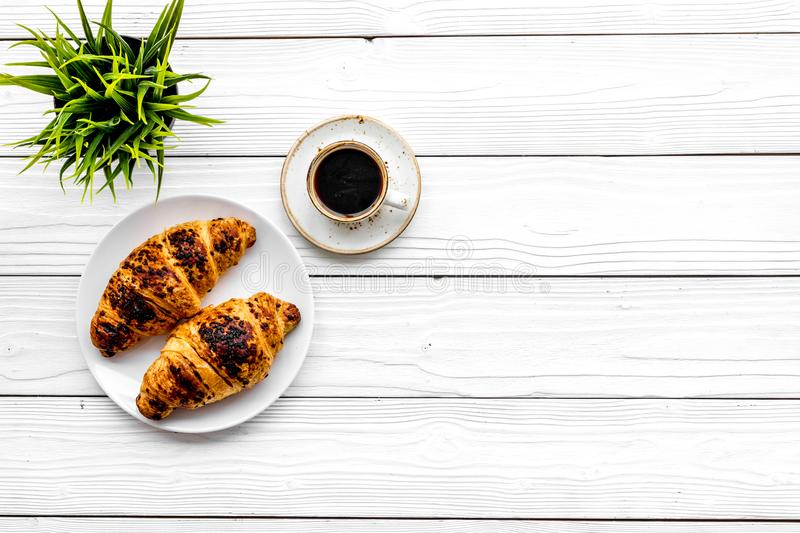 Light breakfast. Small cup of black coffee and croissant on white wooden background top view copyspace. Light breakfast. Small cup of black coffee and croissant royalty free stock photography