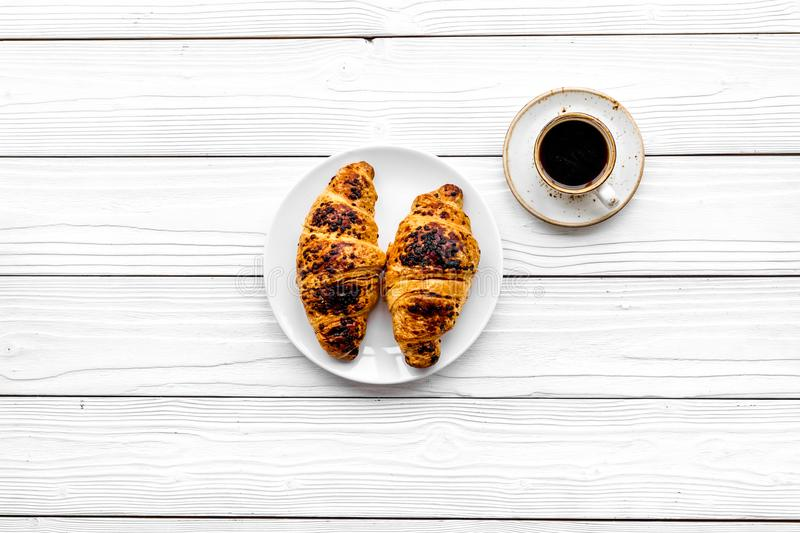 Light breakfast. Small cup of black coffee and croissant on white wooden background top view copy space. Light breakfast. Small cup of black coffee and croissant stock photo