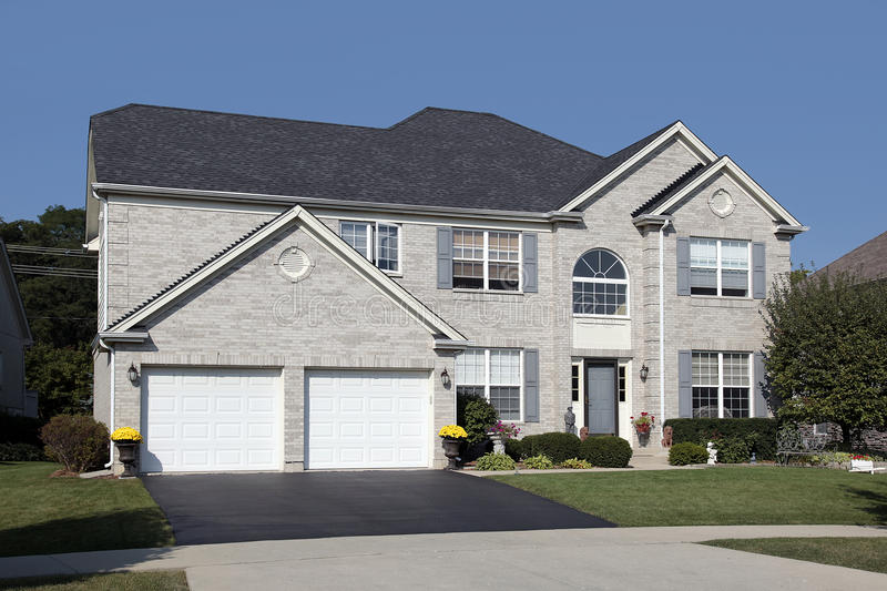 Light brick home with double arched garage stock photo for Brick garages prices
