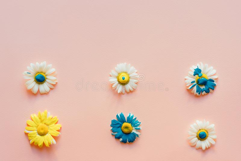 Light bright juicy background with place for text and flower heads of daisies with flowing liquid paint. royalty free stock photo