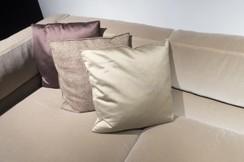 Stylish coach with three decorative pillows in a row. Light brown coach with 3 pillows at one corner royalty free stock photo