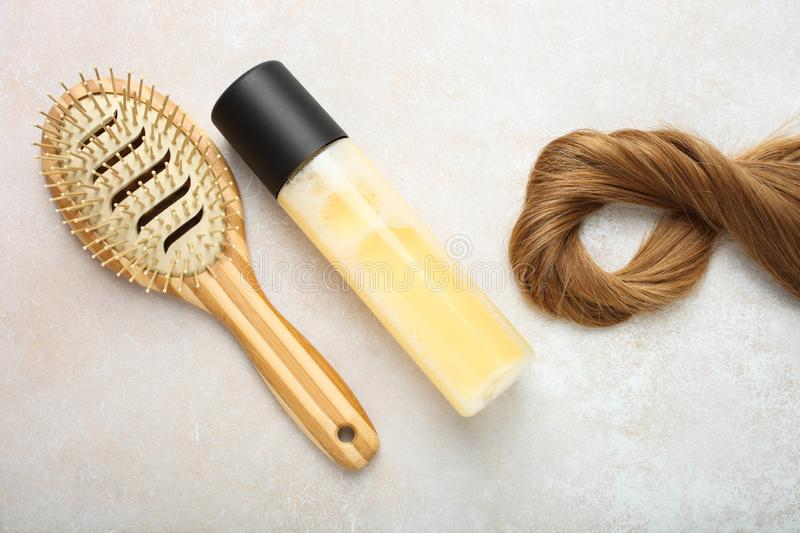 Light brown hair, bamboo comb and hair spray. Lock of female light brown hair, bamboo comb and hair spray on neutral background. Top view stock photos