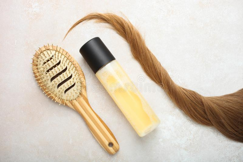 Light brown hair, bamboo comb and hair spray. Lock of female light brown hair, bamboo comb and hair spray on neutral background. Top view stock images