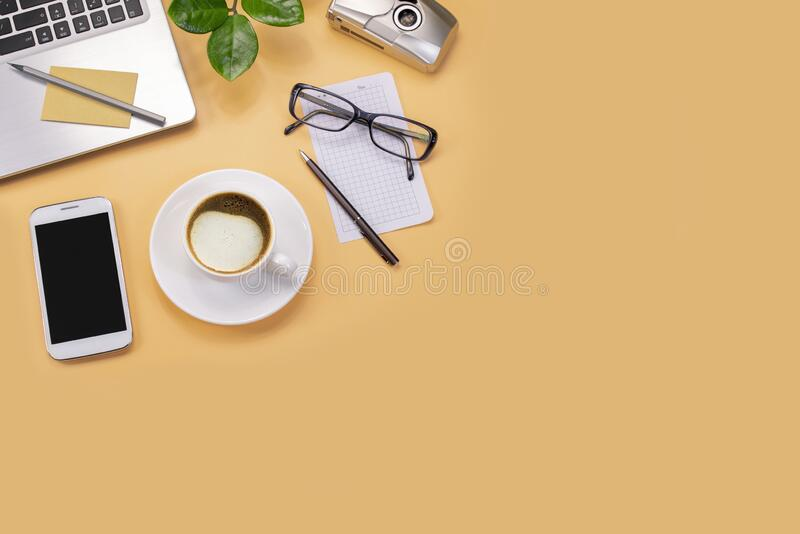 For design light brown office table with laptop, green plant, pen, glasses, camera and cup of coffee. Top view with copy space, fl. Light brown office table with royalty free stock images