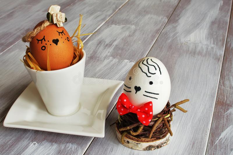 Light brown selfish egg with satin flower in exclusive porcelain coffee pair and white egg with red tie nest from birch twigs on royalty free stock images