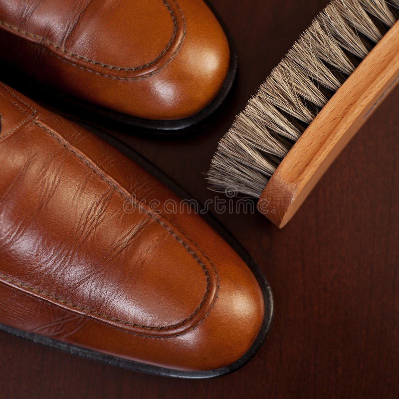 Light brown shoes and brush. Care and polish of leather footwear royalty free stock images