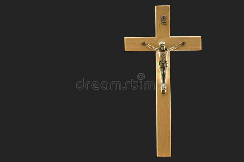 Wooden illuminated crucifix on a black background. A light brown wooden illuminated crucifix against a black background stock image