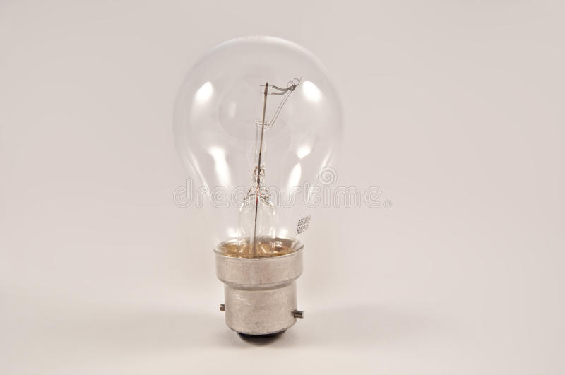 Light bulb. Close on an isolated clear glass light bulb arranged vertically over light grey stock photography