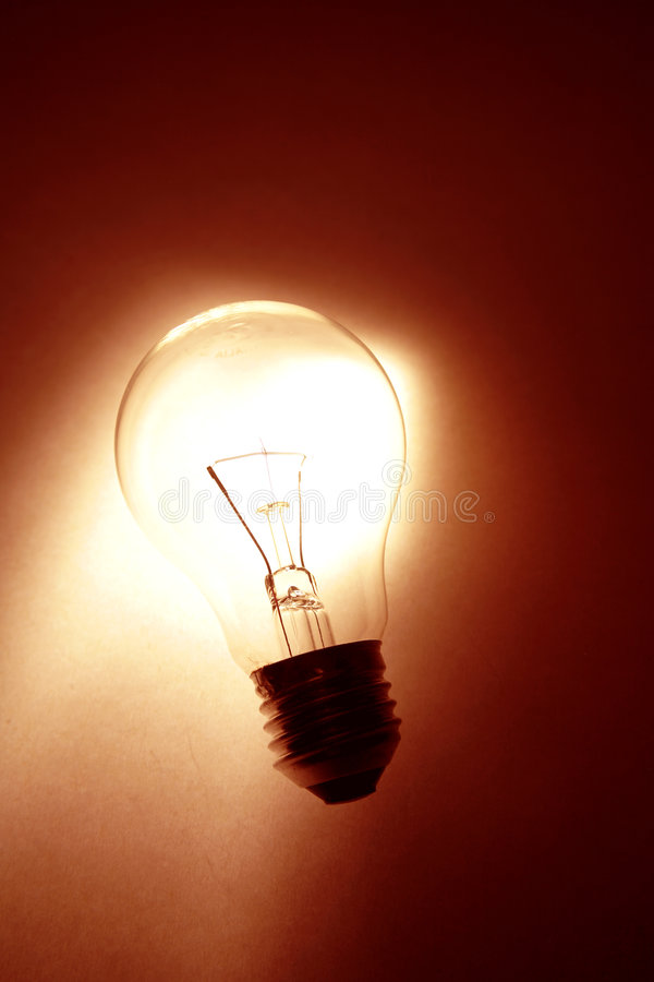 Light-bulb. Clear glass light-bulb glowing closeup royalty free stock image