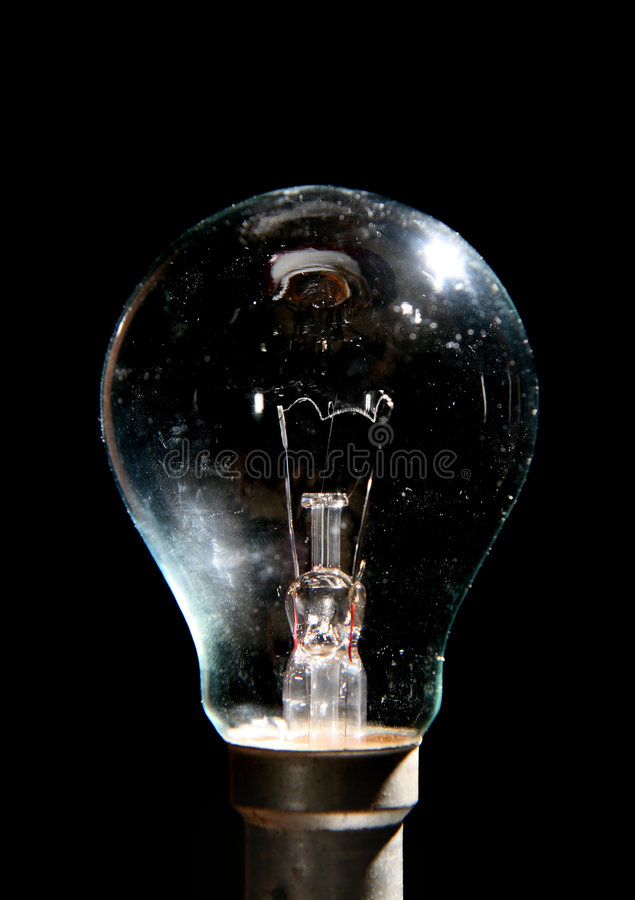 Light Bulb. A light bulb illuminated from the side against black background stock image