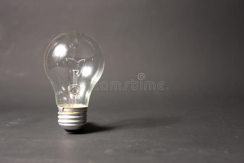 Light bulb alone in black backbround royalty free stock photography