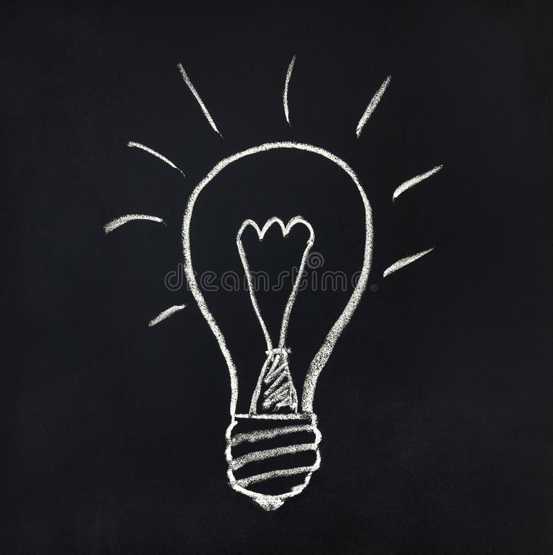 Light bulb on a blackboard royalty free stock images