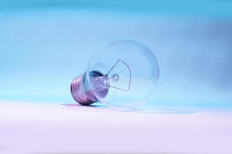 Light bulb. Clear and clean bulb, isolated on nuances of blue and white, symbolizes energy technology stock photos