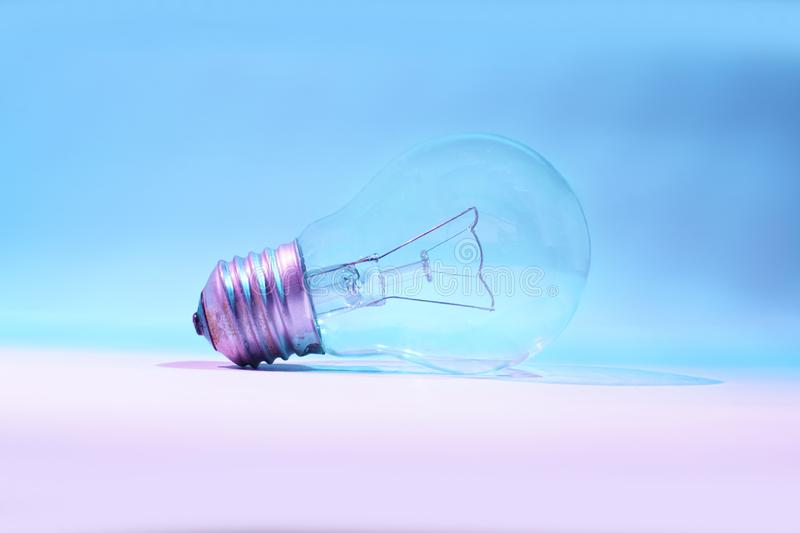 Light bulb. Clear and clean bulb, isolated on nuances of blue and white, symbolizes energy technology royalty free stock photo