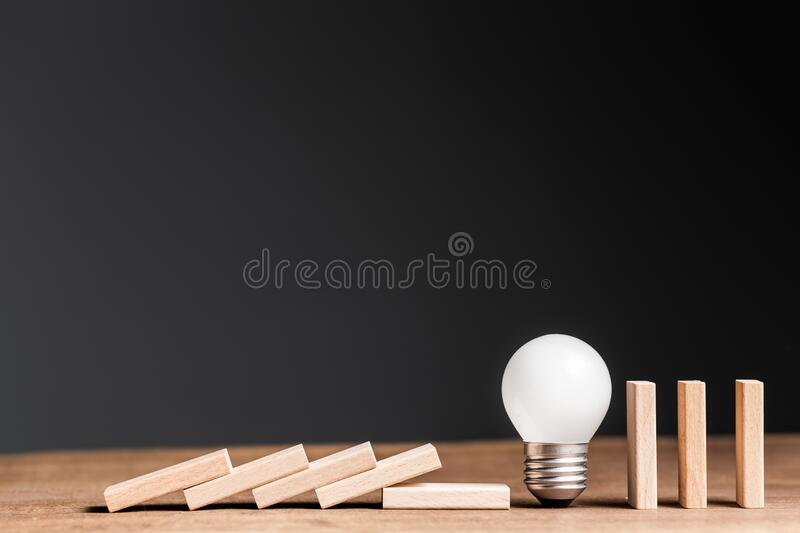 Light Bulb in Falling Domino royalty free stock image
