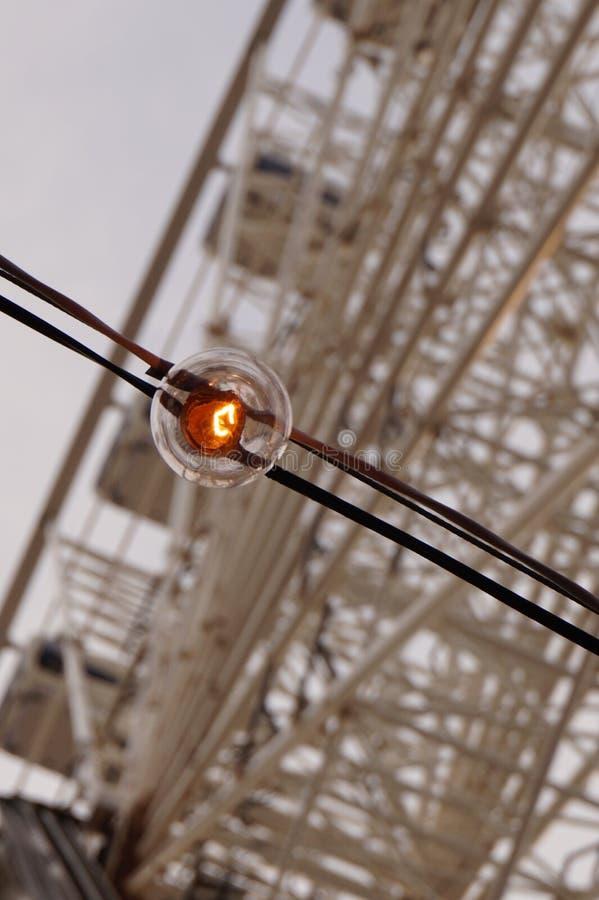 Light bulb by ferris wheel stock photography