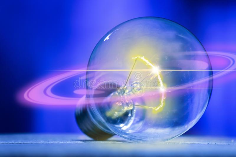 The light bulb with a flash of yellow light in, with a ring of purple light, isolated on electrical technology and business. The light bulb with a flash of stock images