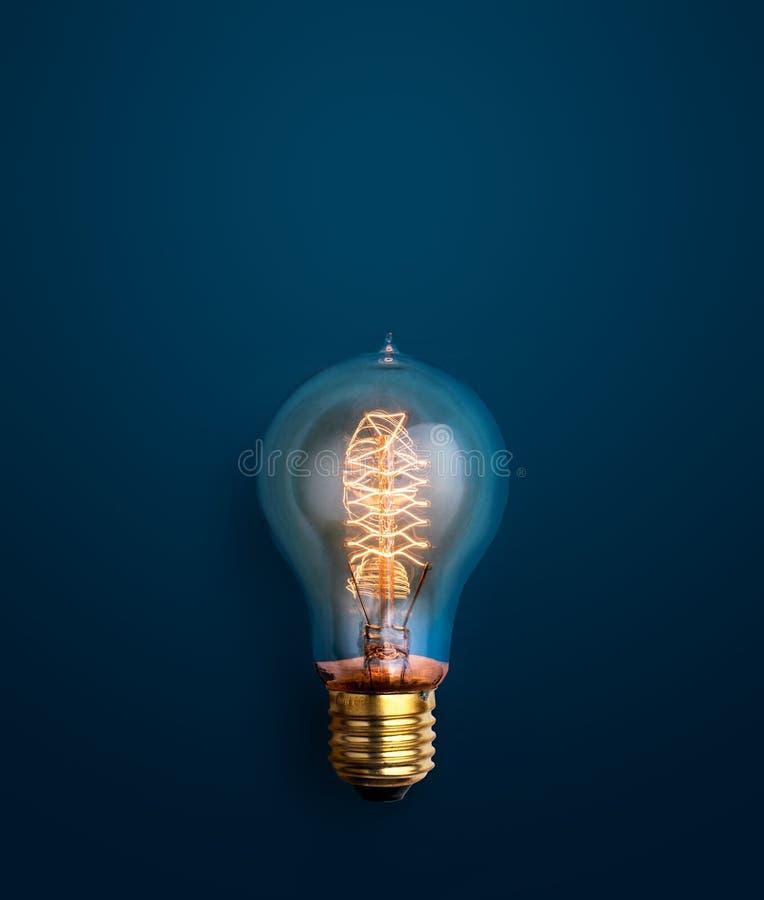 light bulb glowing on blue background creative ideas background stock photo
