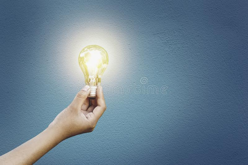 Light bulb hand in hand Cement wall background Energy saving concept. Lightbulb, technology, electricity, holding, object, person, lamp, concrete, texture stock images