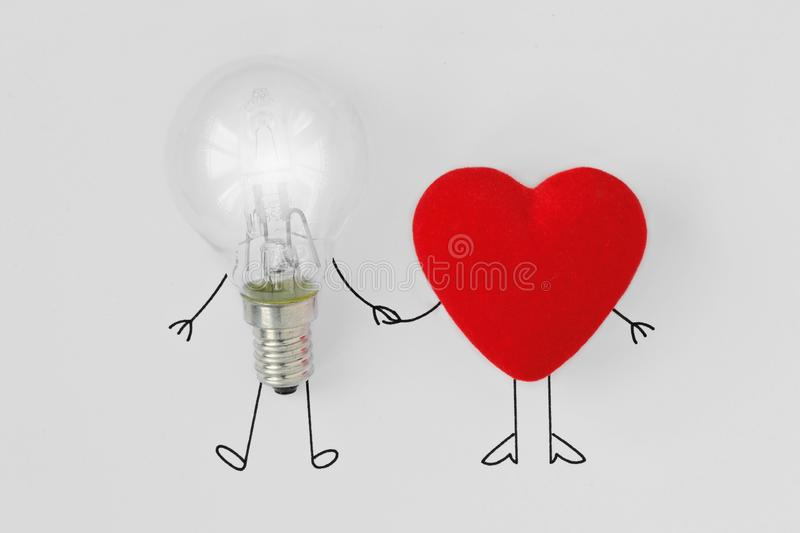 Light bulb and heart holding hands - Concept of brain and heart royalty free stock photos