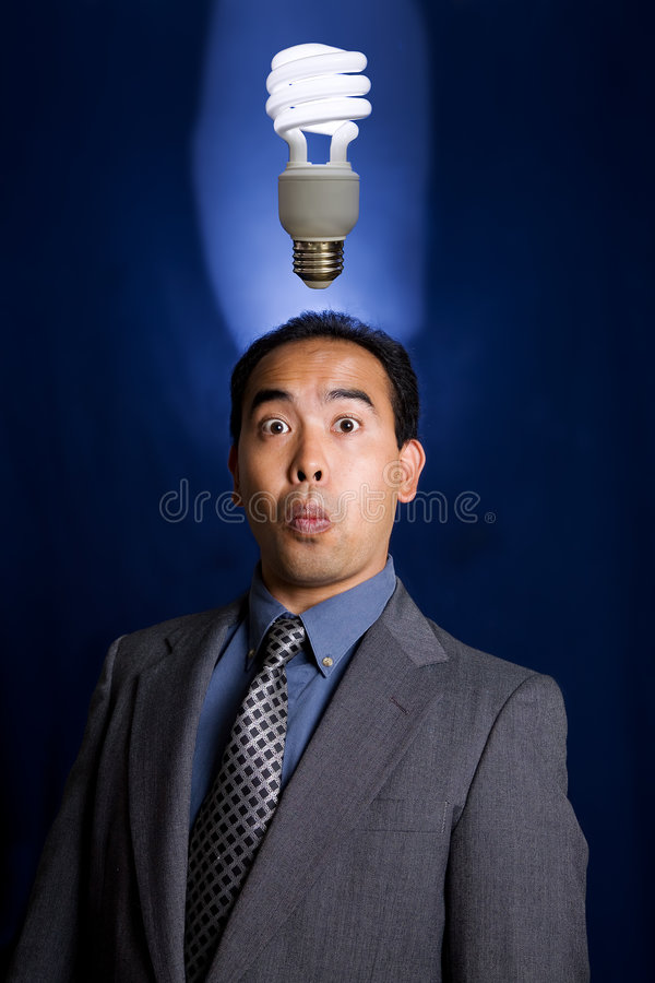 Light Bulb idea 2. Business Man of Asian descent having and idea as shown by a ecofriendly compact fluorescent light bulb above his head stock photo