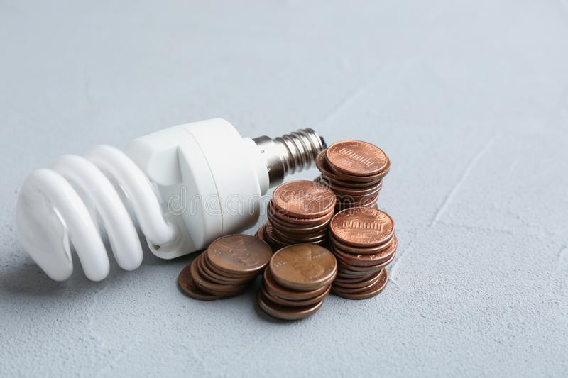 Light bulb and many coins. On table stock image