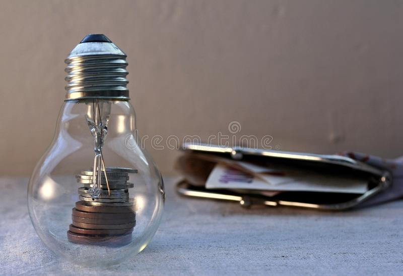 Light bulb, metal coins and wallet with banknotes stock photo