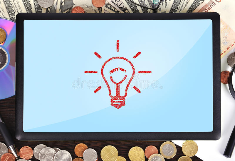 Light bulb. Modern business workplace: tablet with light bulb royalty free stock image