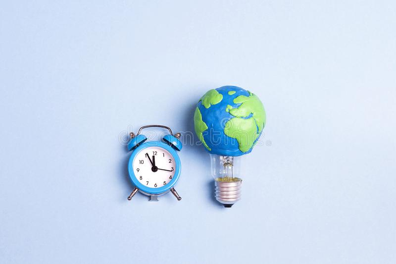 Light bulb with plasticine Earth planet model and alarm clock on yellow background. royalty free stock photography