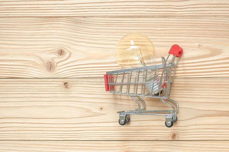 light bulb in shopping cart on wooden background. Energy savings and Ideas royalty free stock image