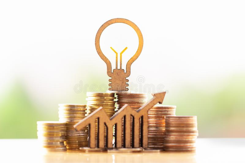 Light bulb and stack of coins in concept of savings and money growing or energy save. stock images