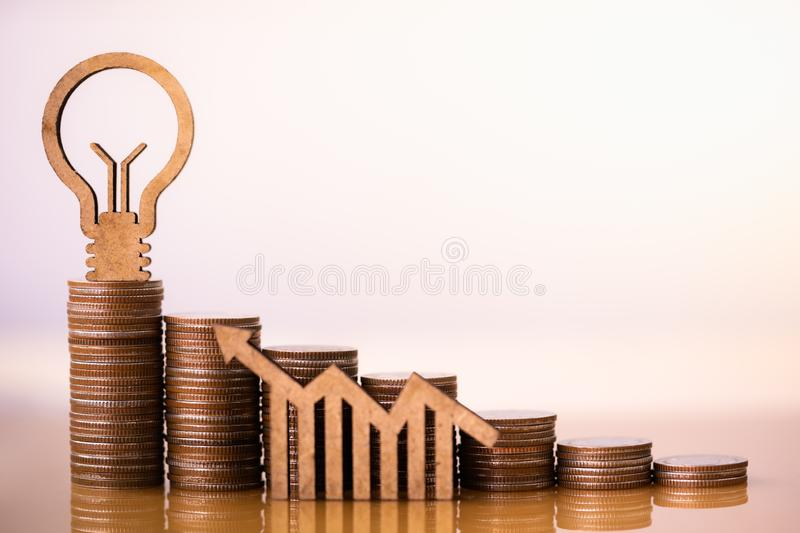 Light bulb and stack of coins in concept of savings and money growing or energy save. Business investment growth concept,money saving and Investment concept stock images