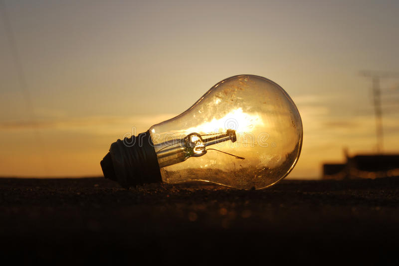 Light Bulb at Sunset on the Clouds Background royalty free stock photo