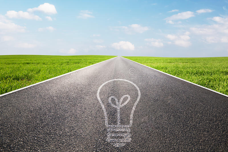 Light bulb symbol on long empty straight road royalty free stock images