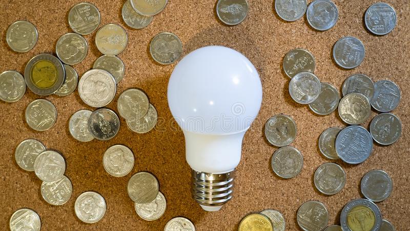 Light bulb and Thai Baht coins money on cork board texture, Innovative idea concept royalty free stock image