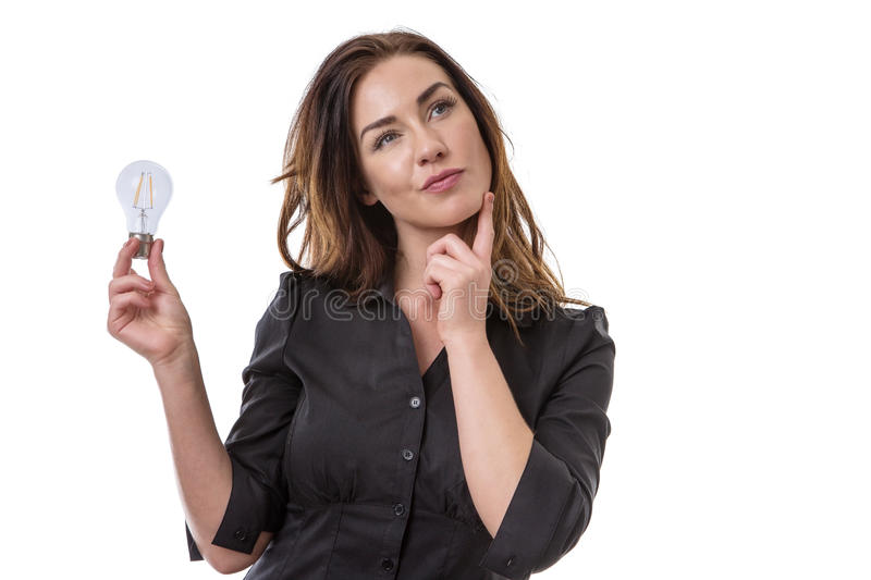 Light bulb thinking. Pretty brunette holding onto a light bulb, looking thoughtful stock photography