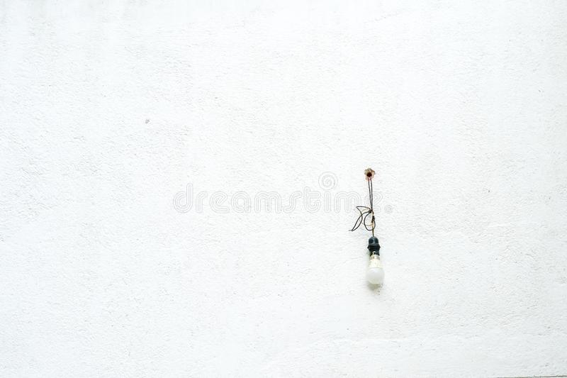 Light bulb on wall. Bare light bulb hanging on grunge white concrete exterior wall with copy space stock photos
