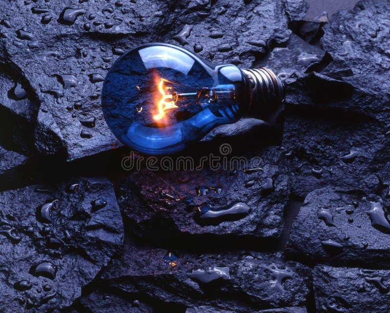 Light bulb on wet rocks stock photography