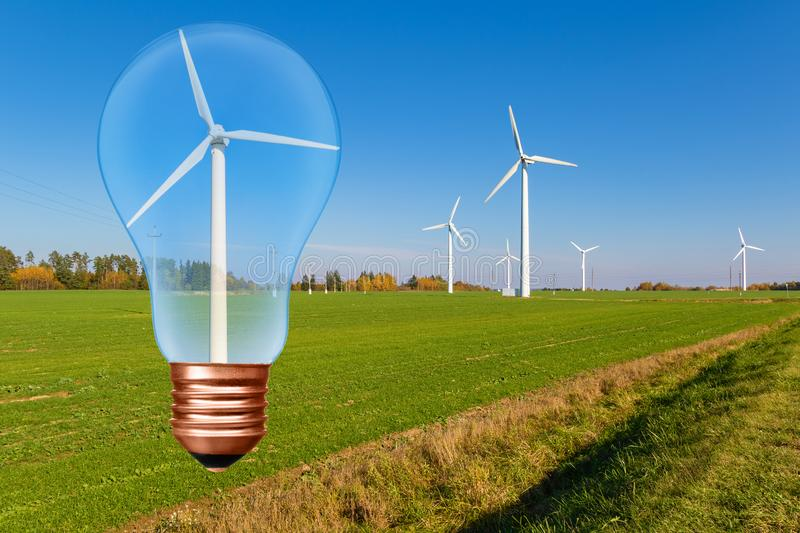 Light bulb with wind turbine inside on the background of blue sky and green field with turbines. royalty free stock photos