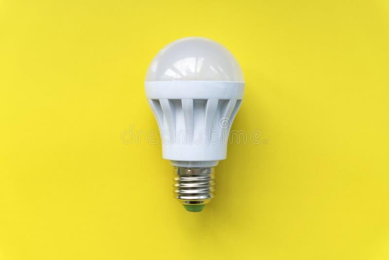Light bulb on yellow background. Fluorescent, energy savings led lamp.  stock photo