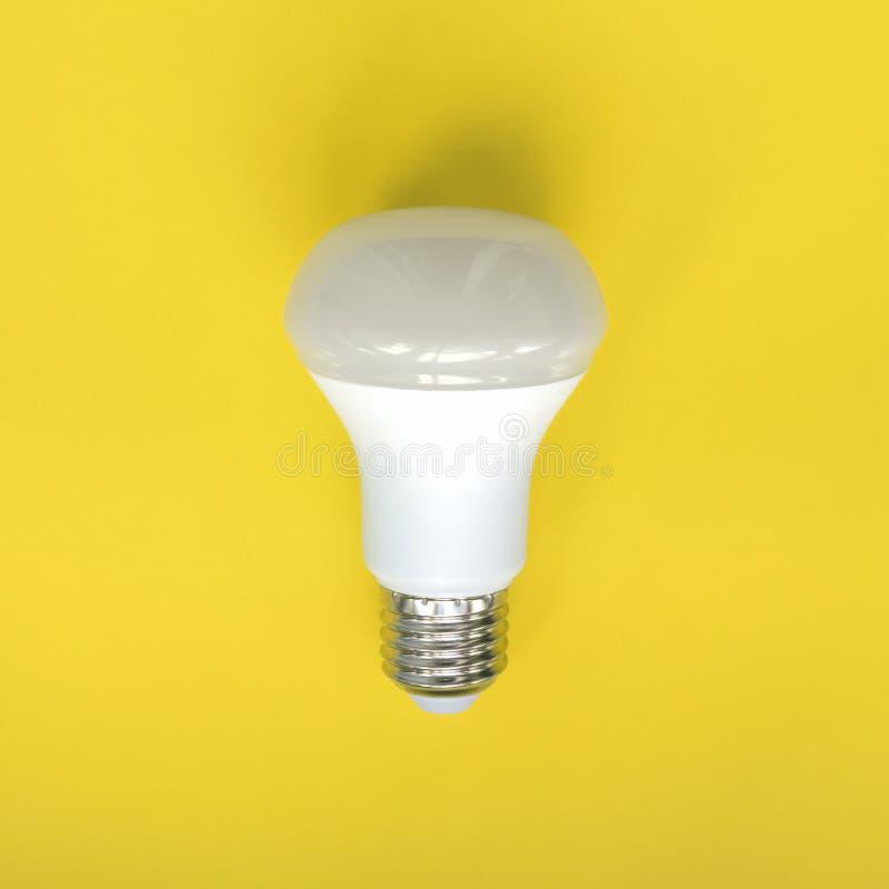 Light bulb on yellow background. Fluorescent, energy savings led lamp.  stock images