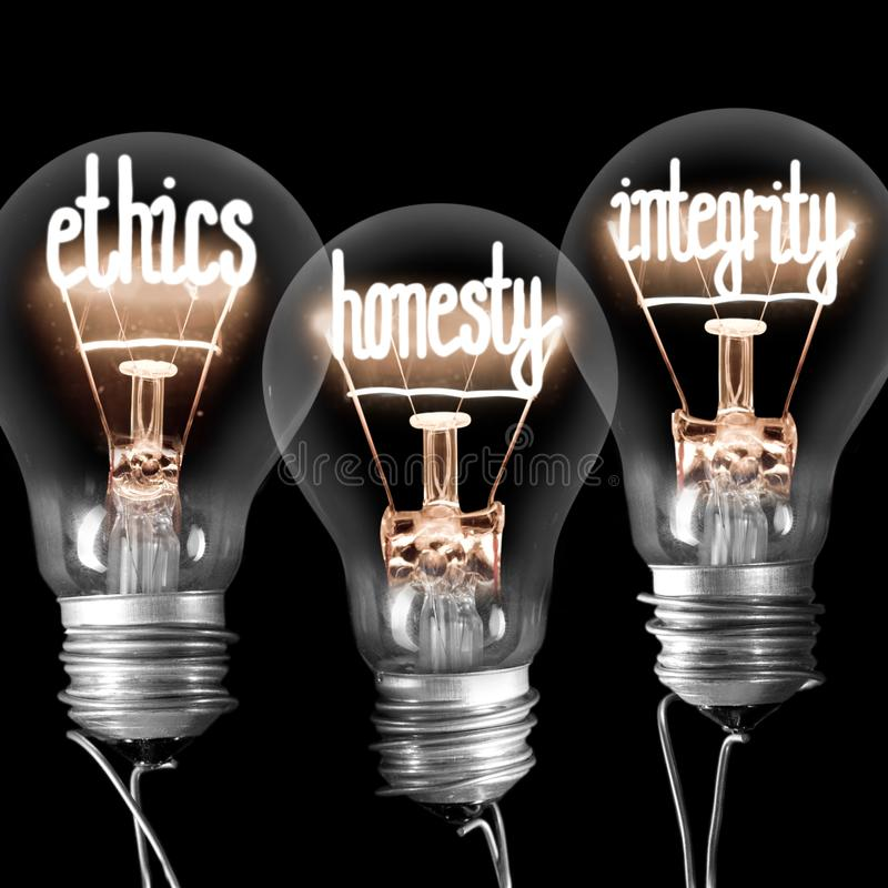 Light Bulbs with Ethics, Honesty and Integrity Concept. Photo of light bulbs with shining fibres in ETHICS, HONESTY and INTEGRITY shape isolated on black royalty free stock image